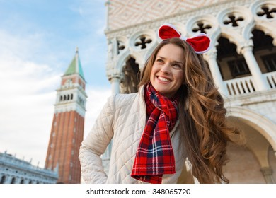 Christmas season brings spirit of travel. Smiling young woman tourist is looking into distance. She is spending Christmas holidays in Venice, Italy - the unique city of water