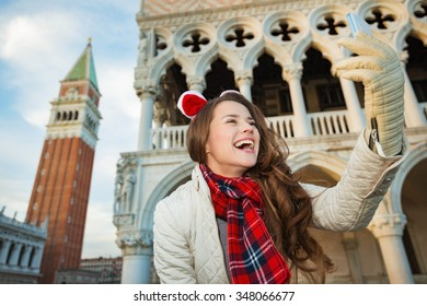 Christmas season brings spirit of travel. Smiling young woman tourist taking selfie while spending Christmas holidays in Venice, Italy - the unique city of water