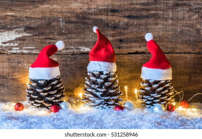 Christmas season, rustic decoration, Santa hats on pine cones with lights at snow and brown wooden background.