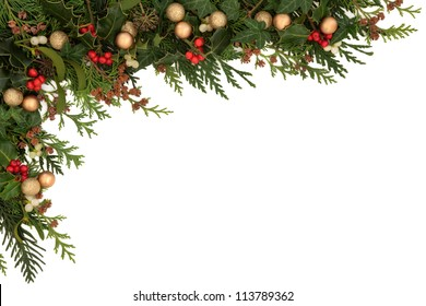 Christmas seasonal  border of holly, ivy, mistletoe, cedar leaf sprigs with pine cones and gold baubles over white background.