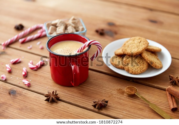 christmas and seasonal drinks concept - red cup of eggnog with candy cane, oatmeal cookies, star anise and cinnamon on wooden background