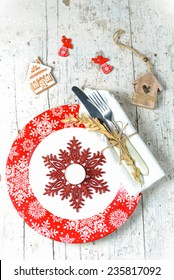 Christmas serving with red snowflake ornament plate, sparkling snowflake decor and tea-candle, with white napkin and cutlery wrapped in it an other christmas decorations