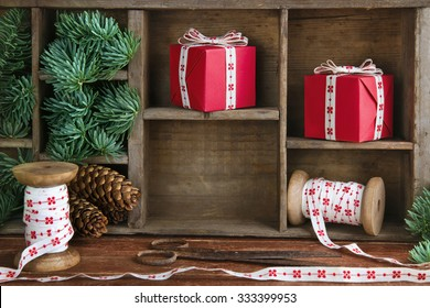 Christmas setting with red Xmas presents, green spruce tree branches and cones on old vintage wooden background, with empty shelf for copy space