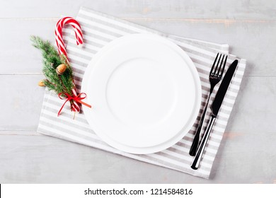 Christmas setting table with Candy cane lollipop and striped napkin. Holiday background with empty plate.