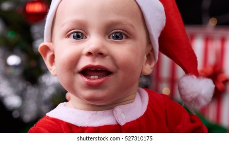 Christmas shoot with cute 9 month old baby boy looking straight at the camera while wearing a santa hat and smiling happily at the camera, with festive decorations in the background.