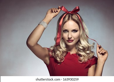 christmas shoot of funny blonde girl with pois bow on her head, adorned like a xmas gift, wearing elegant red dress and bracelet