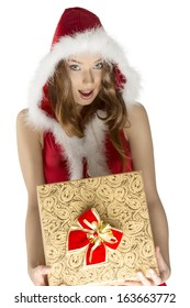christmas shoot of very sexy woman wearing sexy red dress and fur hood, taking pretty gift box in the hands and looking in camera with happy expression