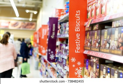 Christmas shoppers in a supermarket aisle with focus on a Festive Biscuits sign.