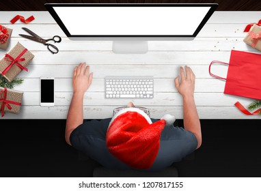 Christmas shopping from the armchair. Man buy gifts online at discounts. Bag, strips and gifts beside. Isolated computer display for mockup.