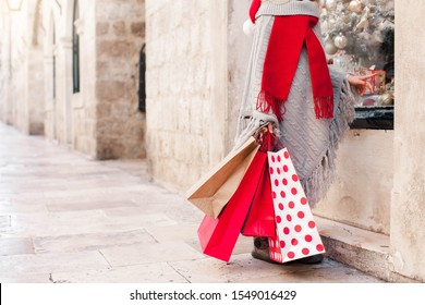 Christmas shopping bags. Child with red paper gifts on market street outside. Funny kid in santa hat by store window. Cozy festive and New Year atmosphere.
