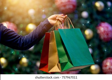 Christmas shopping bags in hand on christmas decoration and light at night on street background