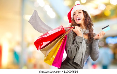 Christmas Shopping. Beautiful Happy Girl With Credit Card In Shopping Mall. Shopping Bags. Shopping Center. Christmas Sales