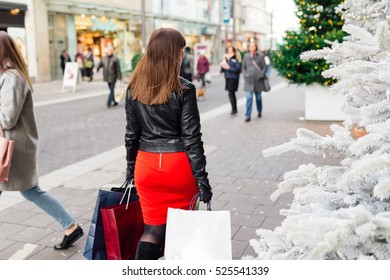 Christmas Shopping. Beautiful Happy Girl with  Shopping Bags. Shopping Center. Christmas Sales