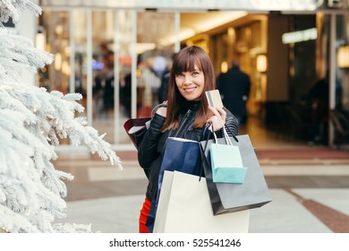 Christmas Shopping. Beautiful Happy woman With Credit Card In Shopping Street. Shopping Bags. Shopping Center. Christmas Sales