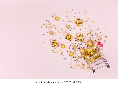 Christmas shopping cart with gift, holiday decorations and golden confetti on pink pastel background top view. Flat lay style.