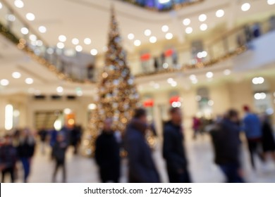 Christmas Shopping Circus: Blurred Scene with dandering Pedestrians around Christmas Decoration Tree in Shopping Mall