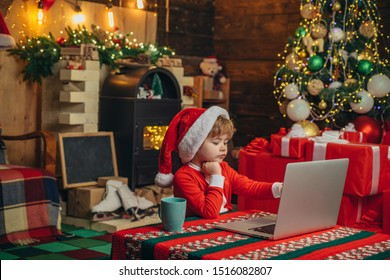 Christmas shopping concept. Gifts service. Little genius. Santa little helper. Little boy santa hat and costume having fun. Boy child with laptop near christmas tree. Buy christmas gifts online.