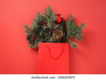 Christmas shopping concept Paper bag full of fir tree and christmas balls with pine cone on red background top view