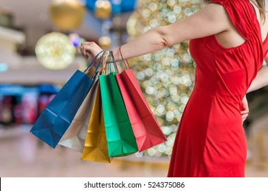Christmas shopping concept. Young woman holds many colorful shopping bags in hand.