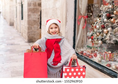 Christmas shopping, gift buying for family and friends. Child girl presents paper bags on market street. Kid in santa hat makes purchase near store showcase. Cozy fair and New Year in Italy or France