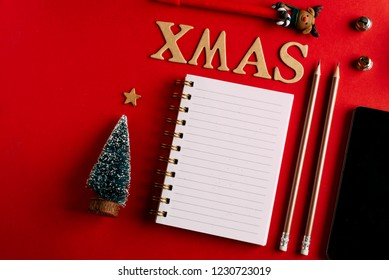 Christmas shopping list and mobile phone, Holiday planning red background, notebook and christmas decoration