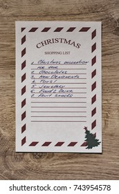 Christmas shopping list on a wooden plank background.