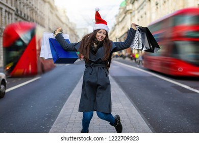 Christmas shopping in London concept: young, attractive woman with red santa hat and shopping bags in her hand on the Regent Street in London, United Kingdom