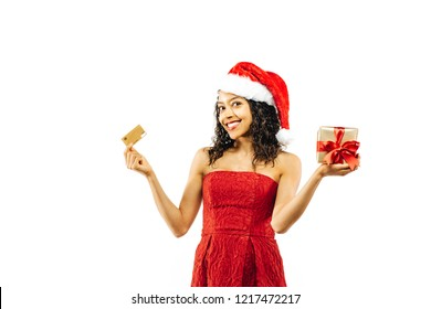Christmas shopping, portrait of a young woman in Santa Claus hat holding a credit card a gift