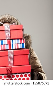 Christmas shopping stress - a woman in a winter anorak is hidden behind a tall stack of colorful decorative Christmas presents as she returns from a day out purchasing gifts