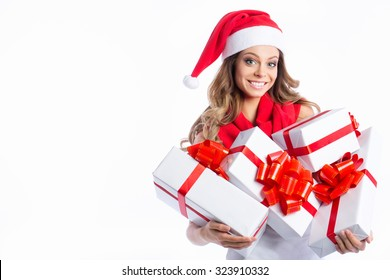 Christmas shopping woman holding many gifts in her arms wearing santa hat.