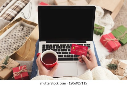 Christmas shopping. Woman ordering presents on laptop and drinking coffee, copy space
