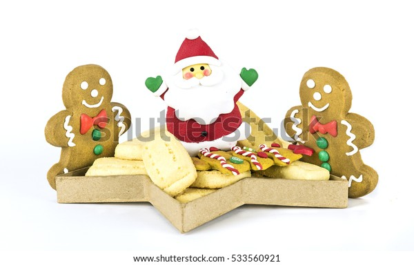 Christmas shortbread cookies in a star shaped box with two gingerbread men and a Santa Claus cookie standing isolated against a white background.