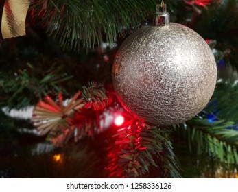 christmas silver decoration with red light on green branch