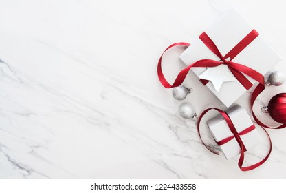 Christmas silver handmade gift boxes on white marble background top view. Merry Christmas greeting card, frame. Winter xmas holiday theme. Happy New Year. Noel. Flat lay