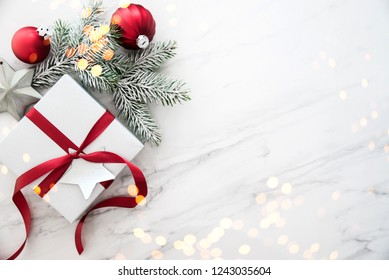 Christmas silver and red gifts and ornaments on white marble background top view. Merry Christmas greeting card, frame. Winter xmas holiday theme. Noel. Happy New Year. Flat lay