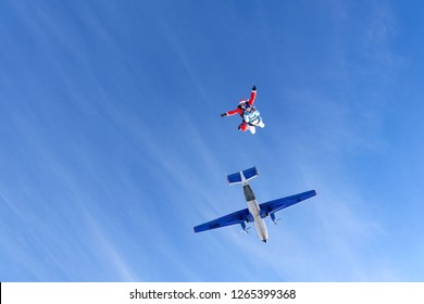 Christmas skydiving. Santa Claus and girl have just jumped out of a plane.