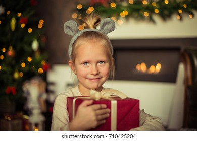 Christmas. Small girl is holding the box with gifts on christmas