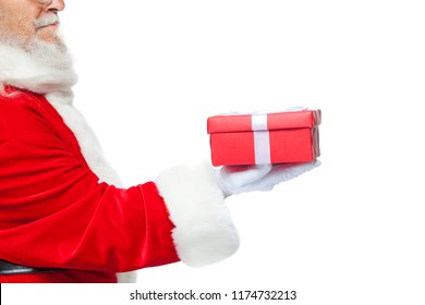 Christmas. Smiling Santa Claus in white gloves is holding a gift red box with a bow. Pointing at the gift. Isolated on white background. Close up