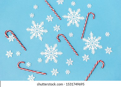 christmas, snow and winter holidays concept - white snowflakes and candy cane decorations on blue background