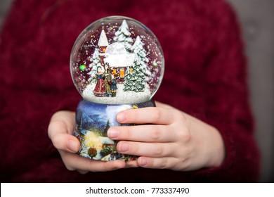 Christmas snowglobe in girl's hands