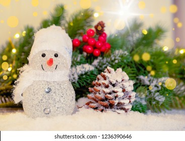 Christmas snowman and cones covered with snow on snow background, close-up