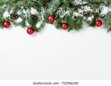 Christmas snowy tree branches and red ornaments on white background