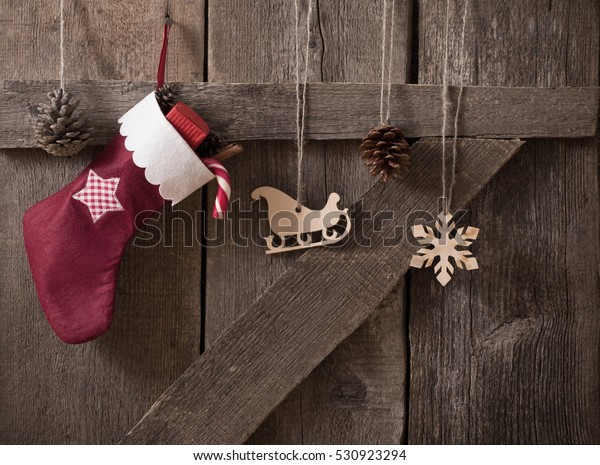 Christmas sock with gifts on  wooden door