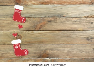Christmas sock, hearts, on wooden background with blank space for ads. Top view.