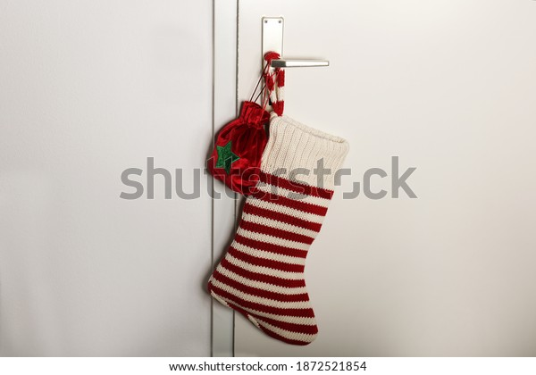 A Christmas sock with red stripes for Christmas gifts hanging on the door. Holiday symbol stocking.