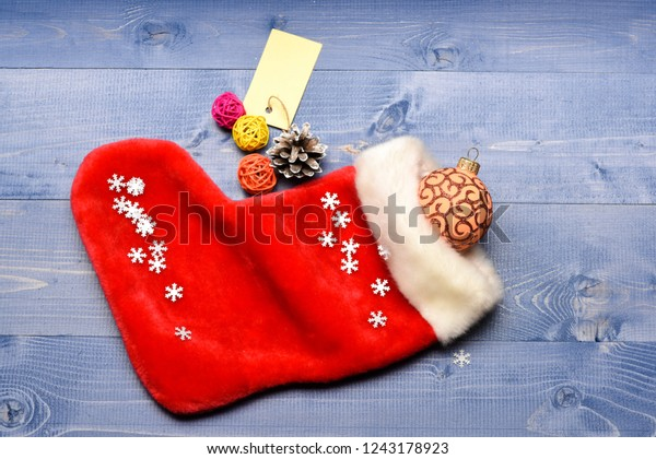 Christmas sock toned wood background top view. Fill sock with gifts or presents. Celebrate christmas. Contents of christmas stocking. Small items stocking stuffers or fillers little christmas gifts.