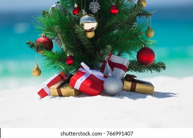 Christmas in some countries is spent in the summer months.  A beautiful christmas tree sits on a white sandy beach under the summer sun.  There are wrapped gifts underneath it.