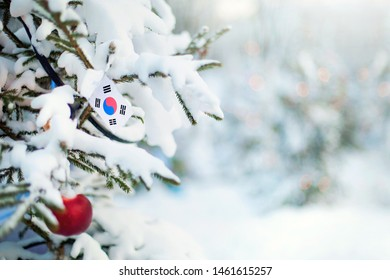 Christmas South Korea. Xmas tree covered with snow, decorations and a flag of South Korea. Snowy forest background in winter. Christmas greeting card.