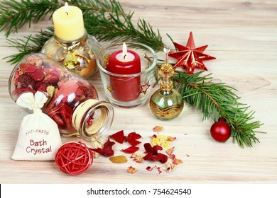 Christmas spa concept with candles and Christmas decoration.  Aromatherapy treatment, aromatic herbs, oil,  bath crystals  on wooden background
