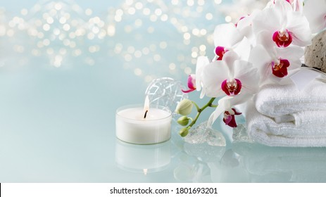 Christmas or spa decoration with white  orchid, soft towel, burning candle on light background with copy space